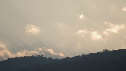 Footage of gentle cloud movement over mountain range in evening