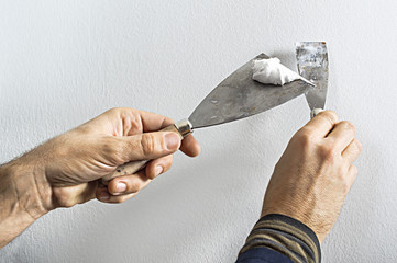 Worker with putty knife working on apartment wall filling