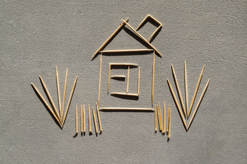 House and grass made of toothpicks on concrete