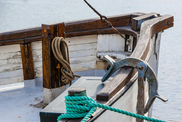 Fishing boat with anchor and ropes in harbor.