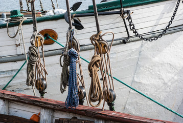 Part of sailing ship with pulleys and knotted ropes.