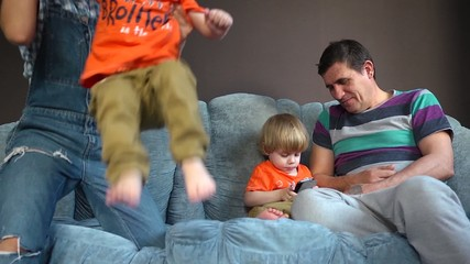 Parents with kids twins playing on a couch - happy family