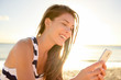 Beautiful young woman on beach with smart phone