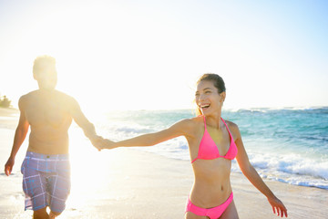 Pretty couple holding hands on beach woman smiling
