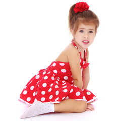 cute little girl sitting on the floor in a beautiful pose.
