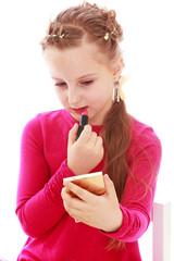 elegant little girl paints lips with lipstick.