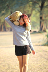 cute asian girl holding teddy bare in the park