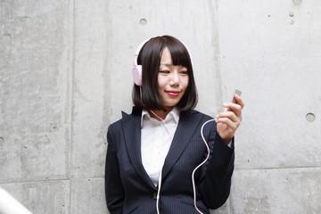 階段で音楽を聴く女性
