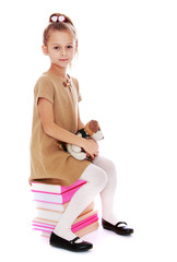 romantic little girl sitting on a pile of books.