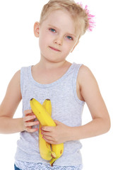 thoughtful little girl with a banana in his hand.