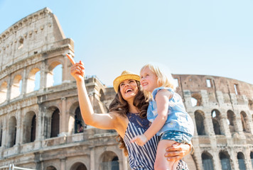 Happy mother and baby girl sightseeing near colosseum in rome