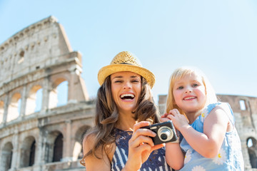 Happy mother and baby girl with photo camera near colosseum