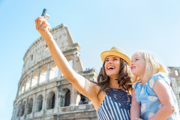 Happy mother and baby girl making selfie in front of colosseum