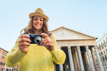 Portrait of happy woman checking photos in camera  in Rome