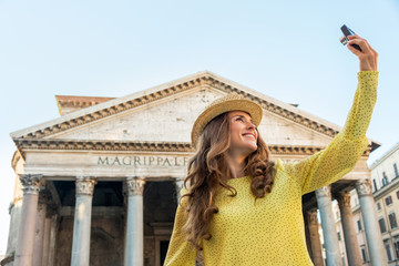 Happy young woman making selfie in front of pantheon in rome
