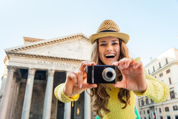 Smiling young woman taking photo in front of pantheon in rome
