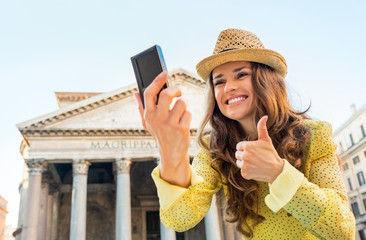 Happy woman making selfie and showing thumbs up in Rome