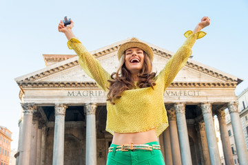 Portrait of happy woman with photo camera rejoicing  in Rome