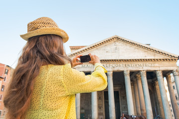 Young woman taking photo of pantheon in rome, italy