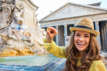 Woman showing coin near fountain of the pantheon  in Rome