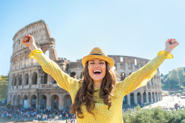 Portrait of happy young woman rejoicing in front of colosseum