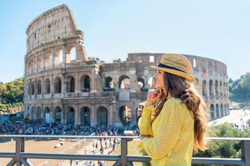 Portrait of thoughtful young woman in front of colosseum in rome