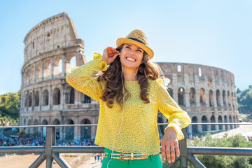Happy young woman with audio guide in front of colosseum in rome