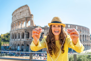Happy young woman giving headphones with audio guide  in Rome