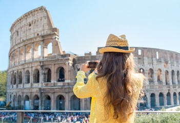 Young woman taking photo of colosseum in rome, italy. rear view