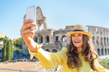 Smiling young woman taking photo with cell phone in Rome
