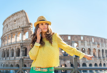 Young woman talking cell phone in front of colosseum in rome