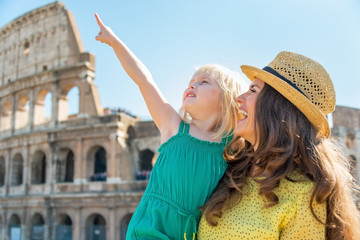 Happy mother and baby girl pointing in front of colosseum