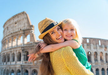 Portrait of mother and baby girl hugging in front of colosseum