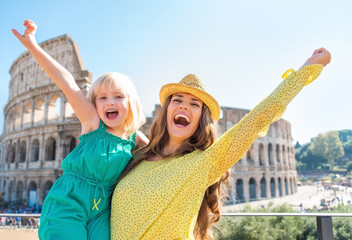 Happy mother and baby girl rejoicing in front of colosseum