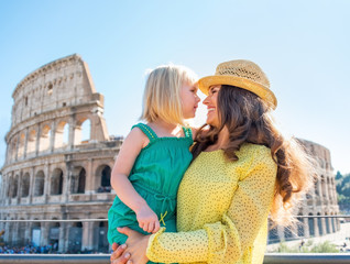 Mother and baby girl in front of colosseum in rome, italy
