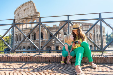 Mother and baby girl sitting in front of colosseum in rome