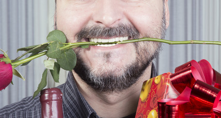 Cropped image of man holding wine present and one rose