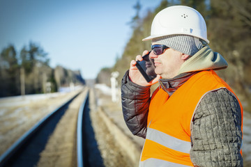 Railway engineer talking on the cell phone on railway
