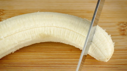 Slow motion macro closeup of chopping fresh banana with knife