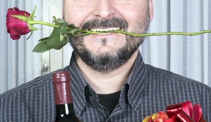 Detail of man holding wine present and one rose