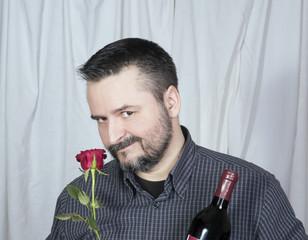Male smelling rose holding bottle of wine