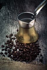 Coffee turk and coffee beans on old gray wooden table with burla