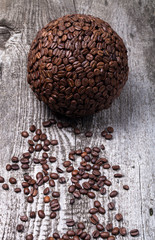 Sphere of coffee and coffee beans on old gray wooden table