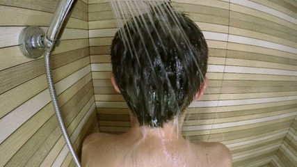 Rear view of man in shower, slow motion