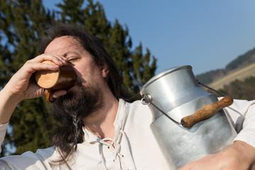 Traditioneller Milchbauer trinkt in der Natur Milch