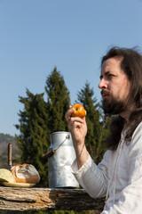 Bärtiger Mann isst Apfel in der Natur