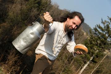 Uriger Bauer in der Natur mit Milchkanne und Brot