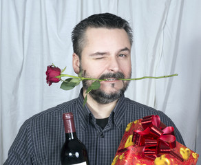 Male winking holding rose in mouth