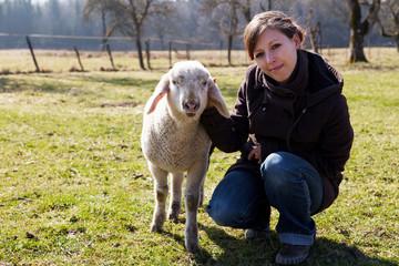 junge Frau mit kleinem Lamm schauen fröhlich