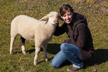 Frau kniet neben kleinem Lamm
